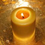Kerze in goldausgelegter Schale